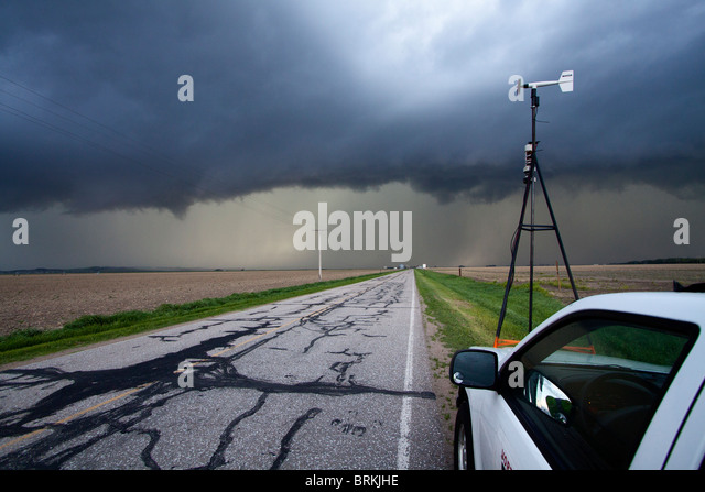 A storm chaser waits alongside the road and watches a severe thunderstorm in rural Nebraska, May 24, 2010. - Stock Image