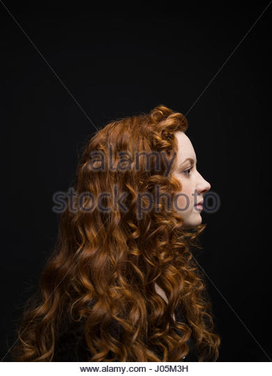 Profile portrait serious woman with long curly red hair against black background - Stock Image