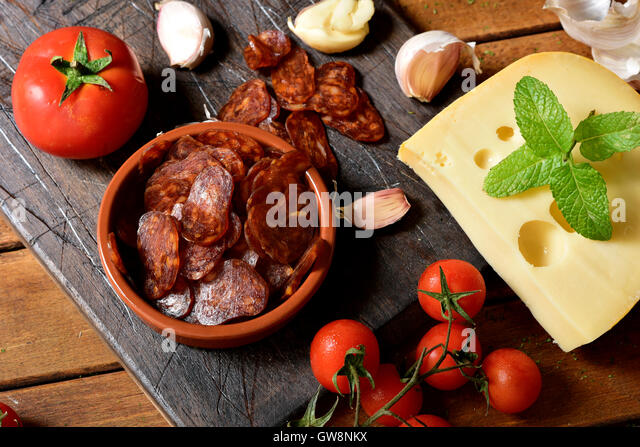 high-angle shot of an earthenware bowl with some slices of Spanish chorizo, a pork sausage typical of Spain, on - Stock Image