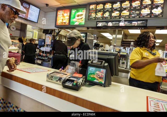 Springfield Illinois McDonald's fast food restaurant counter senior woman employee working Black man customer - Stock Image