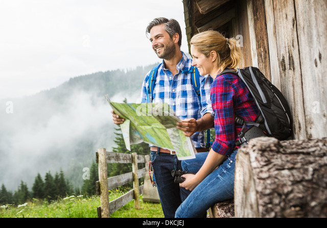Couple with map embarking on trek, Tirol, Austria - Stock Image