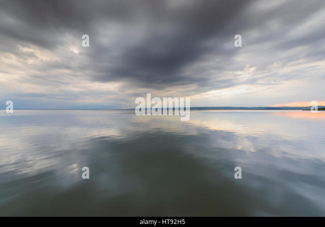 Clouds Reflecting in Lake Neusiedl at Sunset at Weiden, Burgenland, Austria - Stock Image