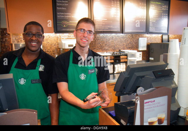 Paris France Europe French 2nd arrondissement Rue des Petits Carreaux Starbucks Coffee Black man coworkers job green - Stock Image