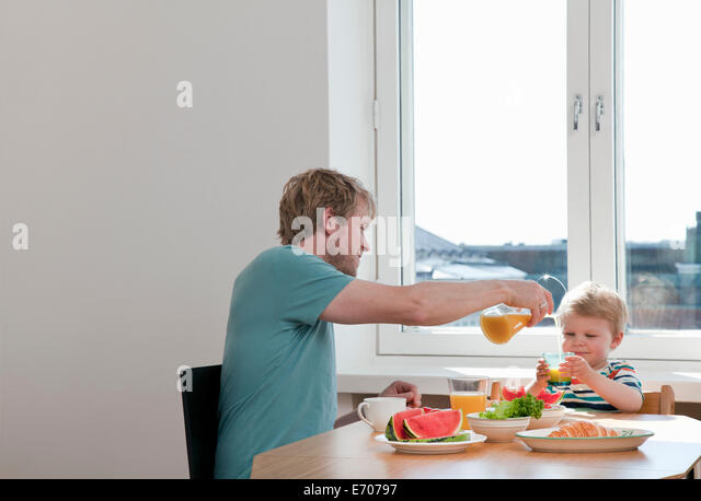 Father and toddler son having breakfast at kitchen table - Stock Image