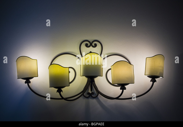 Lit wall lamp in the dark - Stock Image