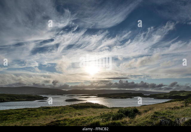 loch dunvegan with cirrus cumulus clouds at sunset with islets - Stock Image