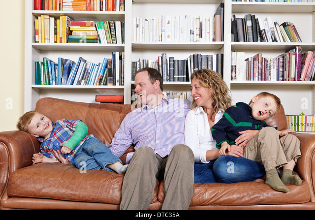 Mid adult parents and young sons having fun on sofa - Stock Image