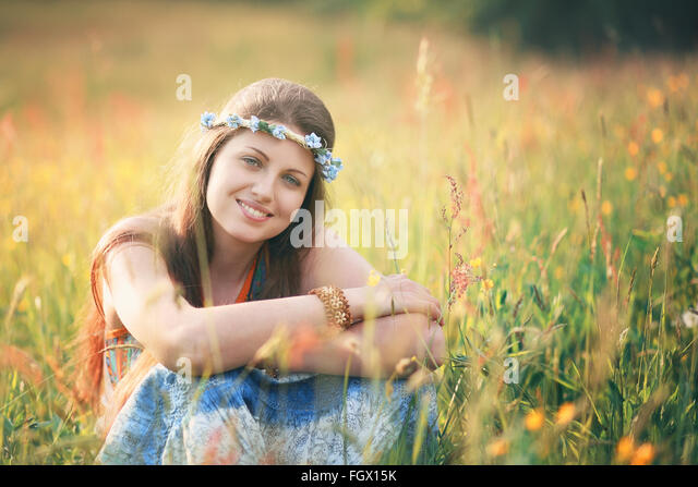 Smiling romantic woman in flower field . Hippie and gypsy dress - Stock Image