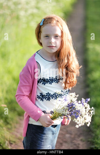 A little girl picking flowers in the countryside. - Stock Image