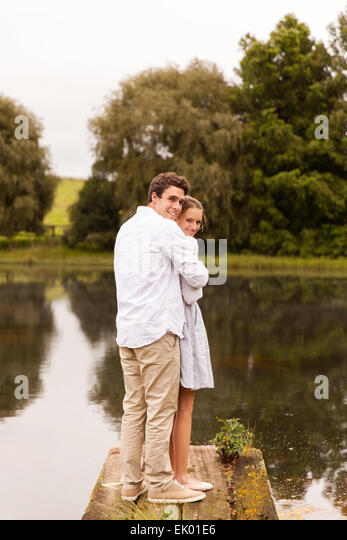 romantic young couple standing on river pier - Stock-Bilder