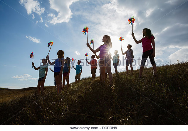 Silhouette of kids holding pinwheels outdoors - Stock Image