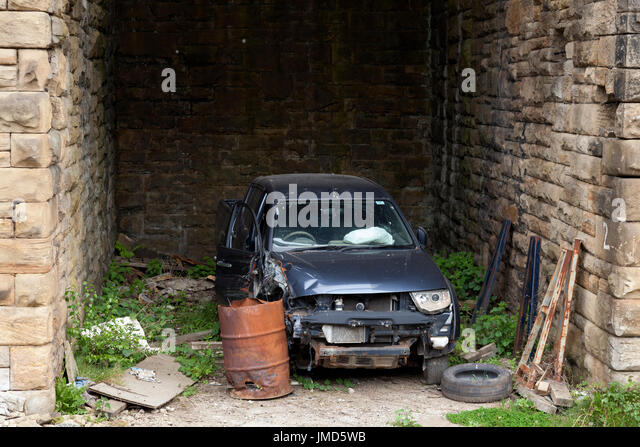 Damaged car under railway arch, Sowerby Bridge, West Yorkshire - Stock Image