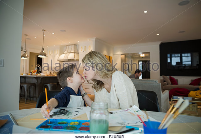Mother kissing son watercolor painting at table - Stock Image