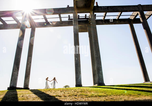 Caucasian brides holding hands walking under concrete structure - Stock Image