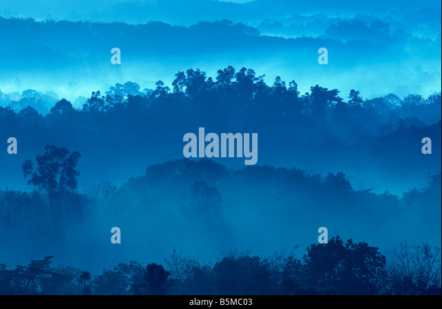 Misty morning of hilly area with ray of light - Stock Image