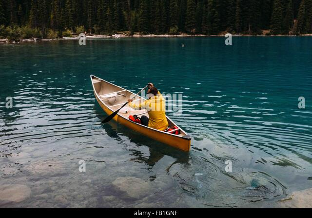 High angle rear view of mid adult man paddling canoe on Moraine lake, Banff National Park, Alberta Canada - Stock Image