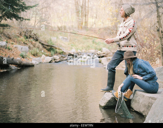 Young couple in a forest, fishing in a river. - Stock Image