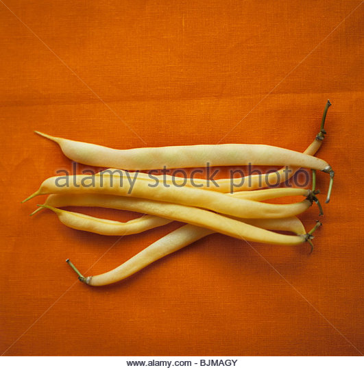 Wax beans against orange background - Stock Image