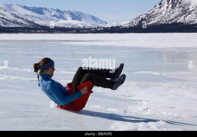 Woman playing, sliding down ice hill on her bottom, overflow, glaciation, ice building up on the shore of Fish Lake, - Stock Image