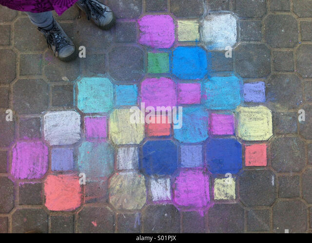 Child chalk painting on the pavement - Stock Image