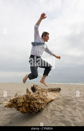 Businessman jumping over a tree trunk on a beach - Stock Image
