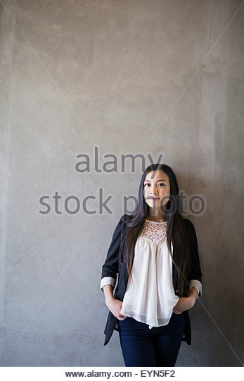 Portrait confident woman hands in pockets gray background - Stock Image