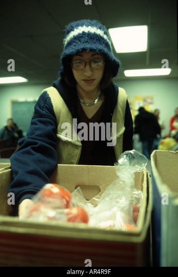 Young female picking through apples at a food bank at a United methodist Church in Lincoln, Nebraska, USA. - Stock Image