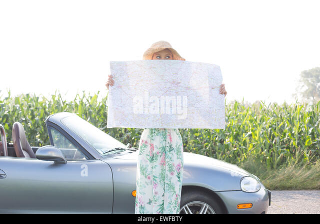 Woman hiding face with map by convertible against clear sky - Stock Image