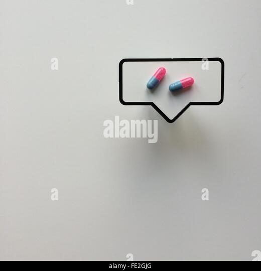 High Angle View Of Capsule In Thought Bubble On White Table - Stock Image