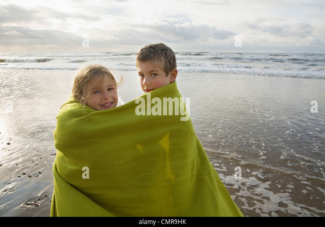 Children in blanket by the sea - Stock Image