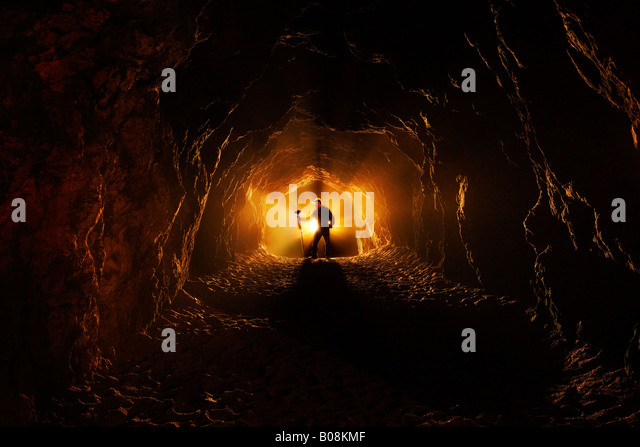A man stands profile view holding a mallet at the end of a dark cave like tunnel where there is a bright light. - Stock Image
