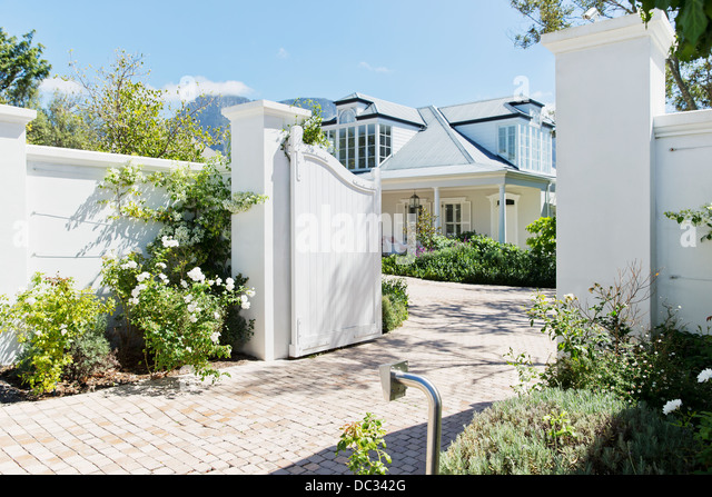 Driveway with open gate to luxury house - Stock Image