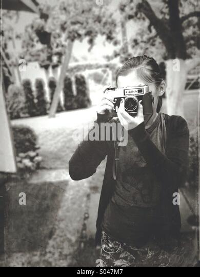 My daughter trying on oldschool russian camera - Stock Image
