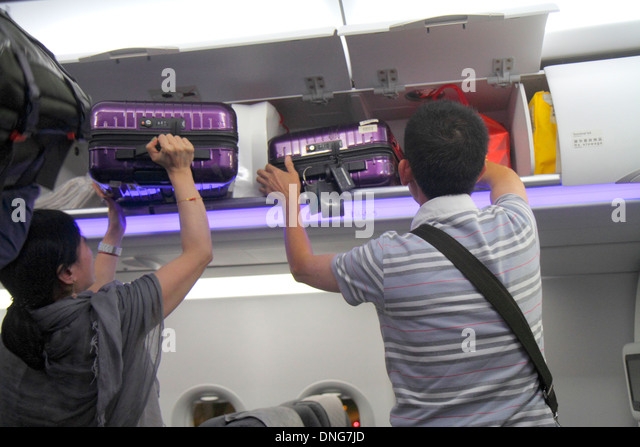 Hong Kong China Hong Kong International Airport HKG Asian man woman removing luggage carry-on overhead luggage bin - Stock Image