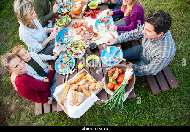 Group of friends celebrating together on garden party - Stock Image