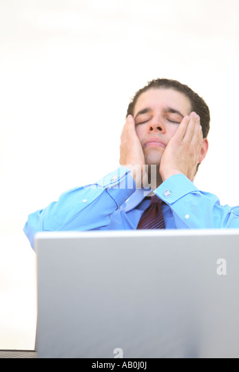 Young businessman working on laptop with frustrated look on face - Stock-Bilder