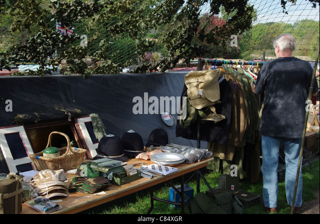A narrowboat selling 40's  gear at a WW2 event at Stoke Bruerne, a purchaser in the background - Stock Image