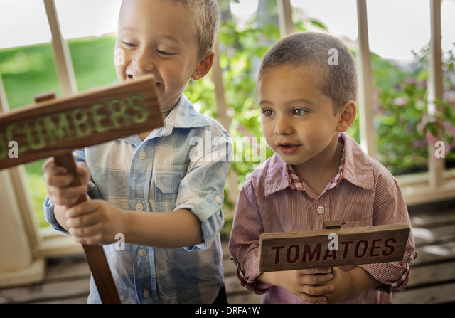 Utah USA Two boys making signs for planted vegetable seeds - Stock Image