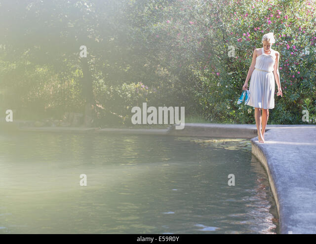 Woman walking by edge of pool - Stock Image