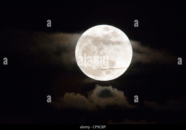 Commercial jet flies in front of a perigree full moon, or supermoon, rising over Salida, Colorado, USA - Stock Image
