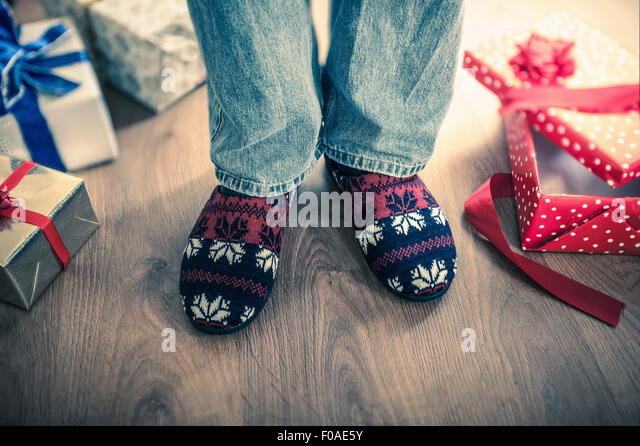 Man wearing slippers with christmas gifts on floor - Stock Image