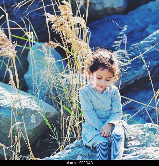 Little Girl on a Rock. Kasairinkai Koen, Tokyo. - Stock Image