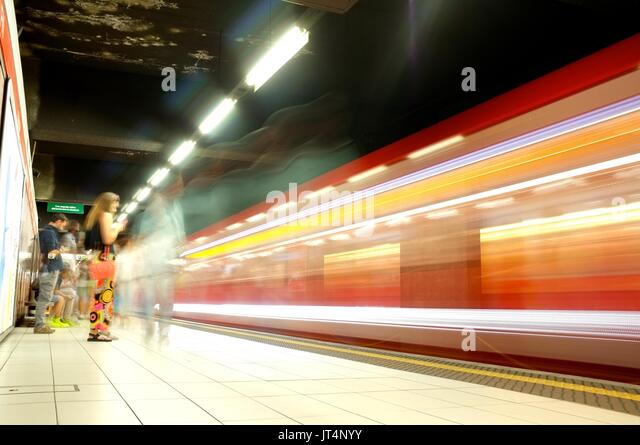 A train passes a platform on the metro underground in Milan, Lombardy, Italy, July 2017 - Stock Image