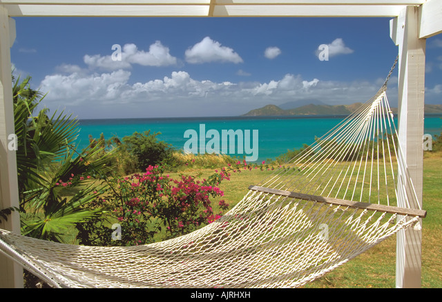 white rope hammock in tropical setting, surrounded by colorful flowers and bright clear water - Stock Image