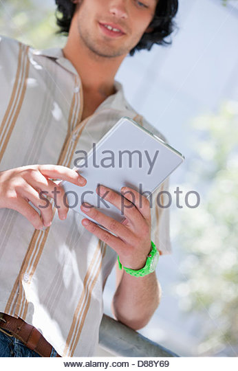 Close up of young man using digital tablet - Stock Image