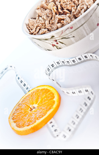 slice of orand , bowl of cornflakes and measuring tape - Stock Image