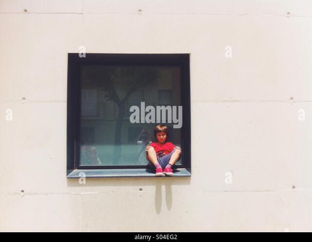Boy sitting on a window - Stock Image