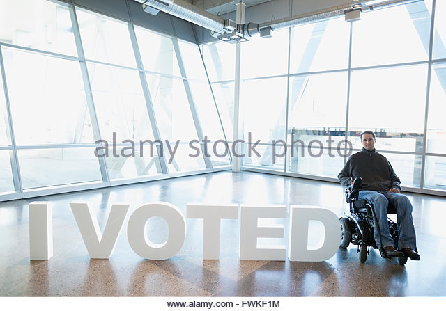 Portrait man wheelchair next to I Voted text - Stock Image