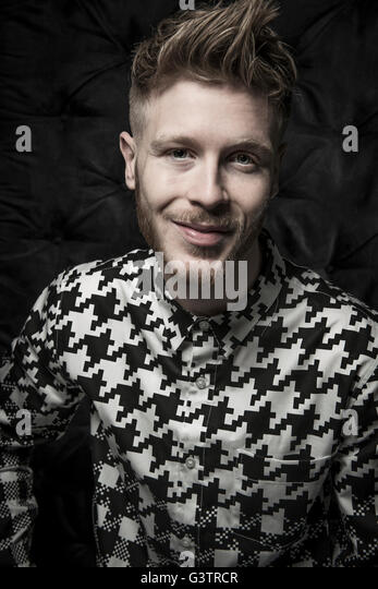 Studio portrait of a bearded young man in a black and white shirt. - Stock-Bilder