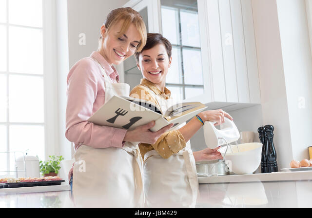 Female caterers with cookbook baking in kitchen, using electric hand mixer - Stock-Bilder